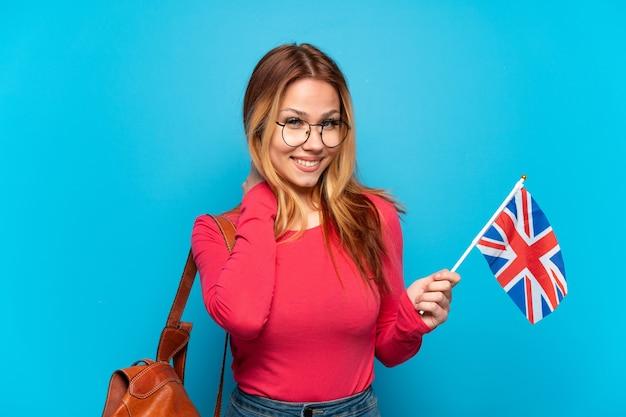 Молодая девушка держит флаг соединенного королевства на изолированном синем фоне, смеясь
