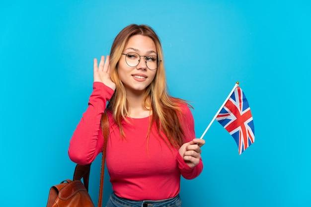 Молодая девушка держит флаг соединенного королевства на изолированном синем фоне, слушая что-то, положив руку на ухо