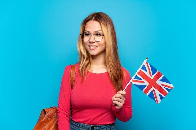 Молодая девушка держит флаг соединенного королевства на изолированном синем фоне, смотрит в сторону и улыбается