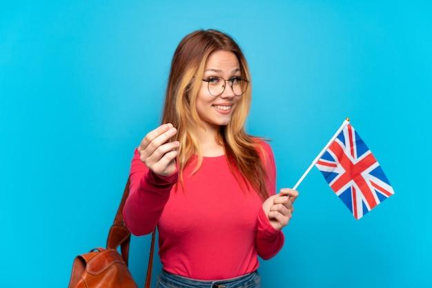 Молодая девушка держит флаг соединенного королевства на изолированном синем фоне, делая денежный жест