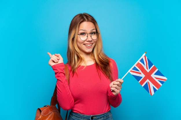 다시 가리키는 격리 된 파란색 배경 위에 영국 국기를 들고 어린 소녀