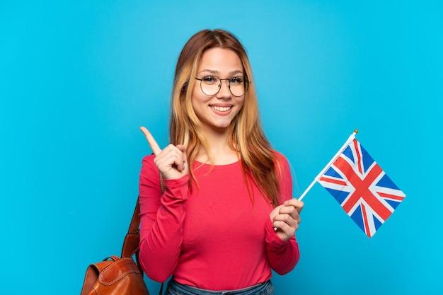 製品を提示する側を指している孤立した青い背景の上にイギリスの旗を保持している若い女の子