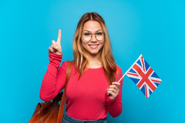 Молодая девушка держит флаг соединенного королевства на изолированном синем фоне, указывая на отличную идею