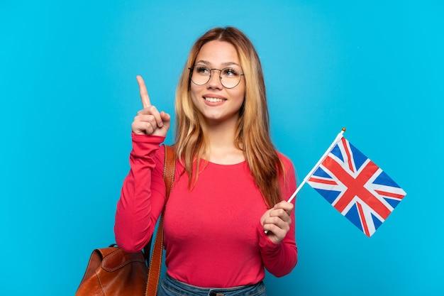 좋은 아이디어를 가리키는 고립 된 파란색 배경 위에 영국 국기를 들고 어린 소녀