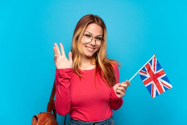 幸せな表情で手で敬礼する孤立した青い背景の上にイギリスの旗を保持している少女