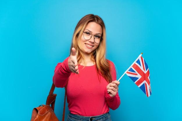 격리된 파란색 배경 위에 영국 국기를 들고 좋은 거래를 성사시키기 위해 악수하는 어린 소녀