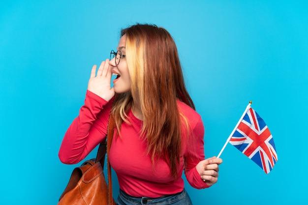 고립 된 파란색 배경 위에 영국 국기를 들고 어린 소녀 입 벌리고 측면으로 외치는