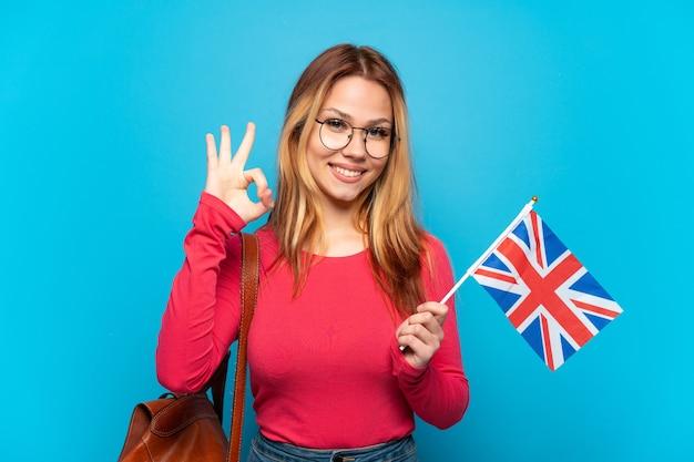 Молодая девушка держит флаг соединенного королевства на изолированном синем фоне, показывая пальцами знак ок