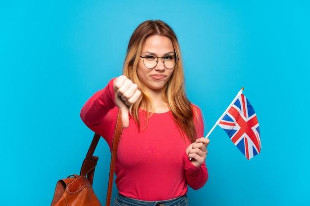부정적인 표현으로 아래로 엄지 손가락을 보여주는 고립 된 파란색 배경 위에 영국 국기를 들고 어린 소녀