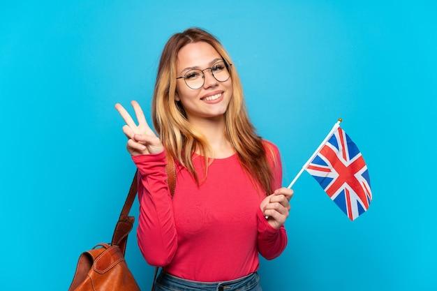Молодая девушка держит флаг соединенного королевства на изолированном синем фоне, улыбаясь и показывая знак победы