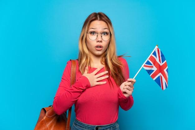 Молодая девушка с флагом соединенного королевства на изолированном синем фоне удивлена и шокирована, глядя вправо