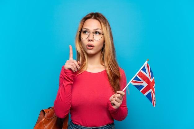 손가락을 가리키는 아이디어를 생각하는 고립 된 파란색 배경 위에 영국 국기를 들고 어린 소녀