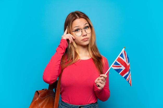 アイデアを考えて孤立した青い背景の上にイギリスの旗を保持している少女