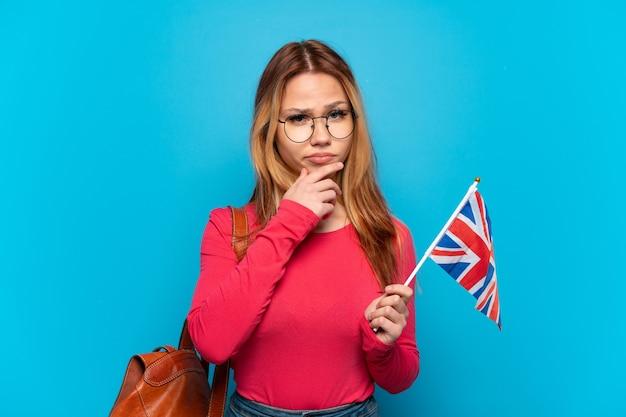 고립 된 파란색 배경 생각에 영국 국기를 들고 어린 소녀