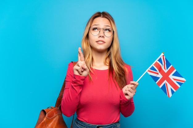Молодая девушка держит флаг соединенного королевства на изолированном синем фоне со скрещенными пальцами и желает всего наилучшего