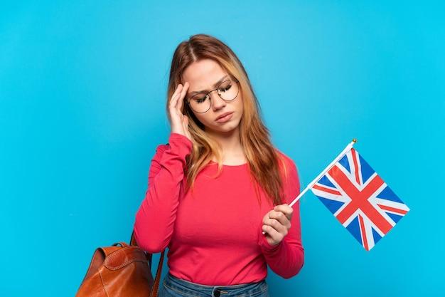 Молодая девушка держит флаг соединенного королевства на изолированном синем фоне с головной болью