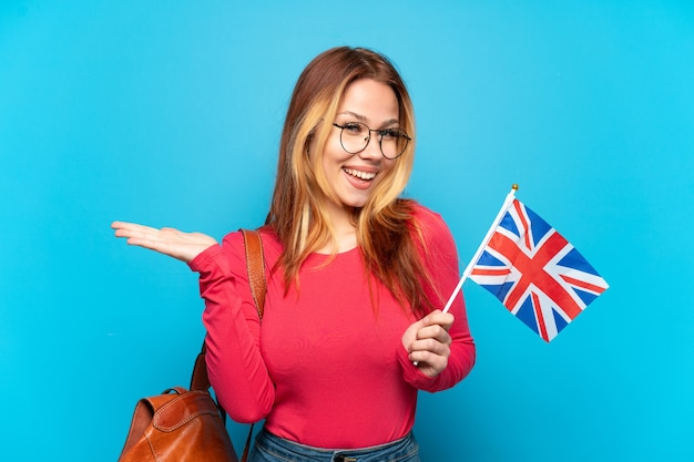 Молодая девушка держит флаг соединенного королевства на изолированном синем фоне с шокированным выражением лица