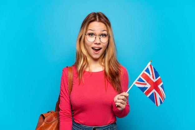 놀라운 표정으로 고립 된 파란색 배경 위에 영국 국기를 들고 어린 소녀