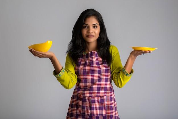 어린 소녀 잡고 회색에 주방 용품 접시와 그릇 포즈