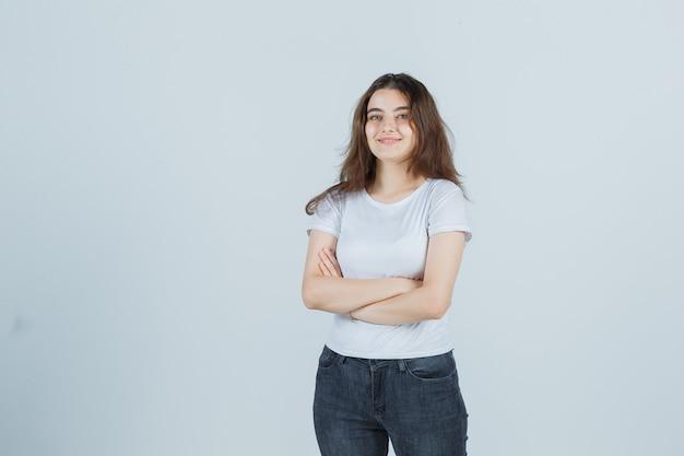 Молодая девушка держит руки, сложенные в футболке, джинсах и выглядит довольным. передний план.