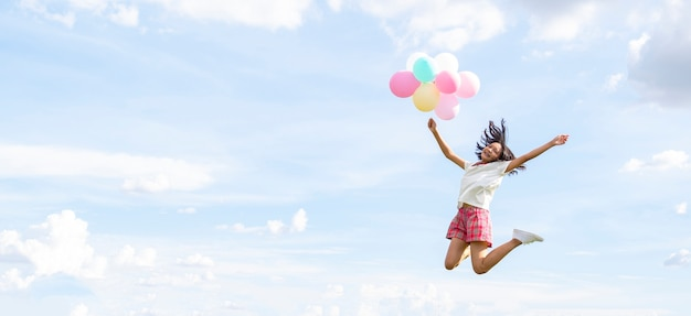 Young girl holding balloons and jumping