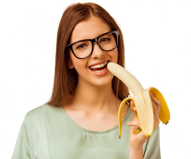 A young girl holding a banana isolated