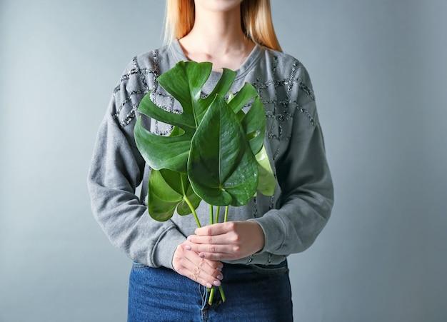 Молодая девушка держит красивые тропические листья на цветной поверхности
