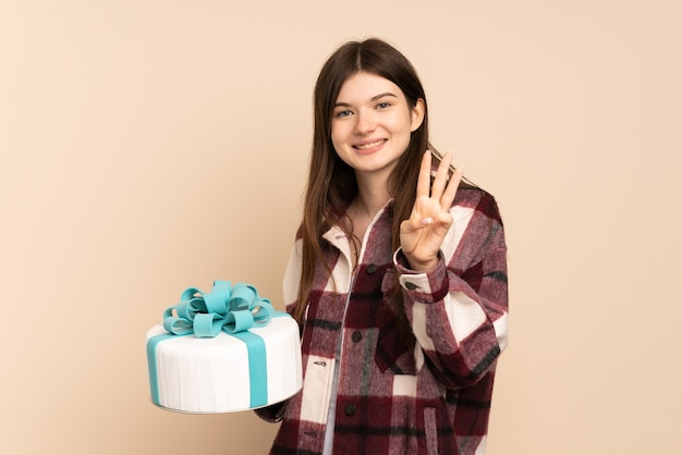 Young girl holding a big cake isolated on beige happy and counting three with fingers