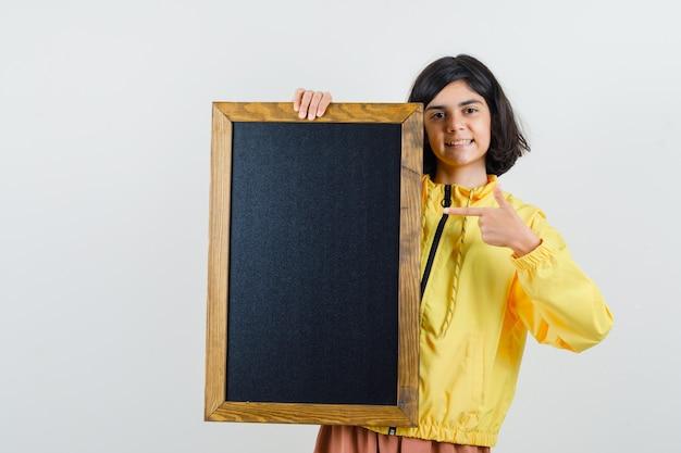 Молодая девушка держит доску, указывая на нее указательным пальцем в желтой куртке бомбардировщика и выглядит счастливой.
