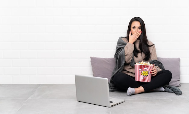 Young girl holding a bowl of popcorns and showing a film in a laptop covering mouth with hands