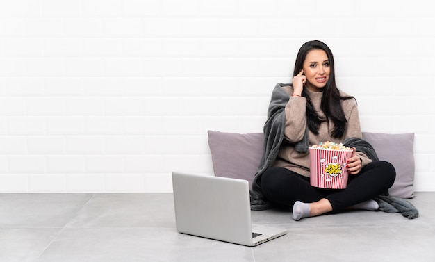 Young girl holding a bowl of popcorns and showing a film in a laptop frustrated and covering ears