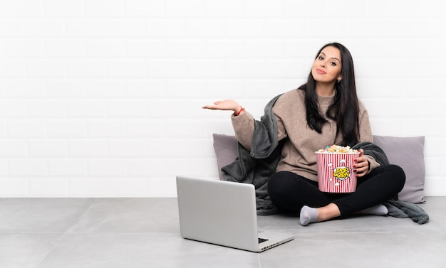 Young girl holding a bowl of popcorns and showing a film in a laptop holding copyspace to insert an ad