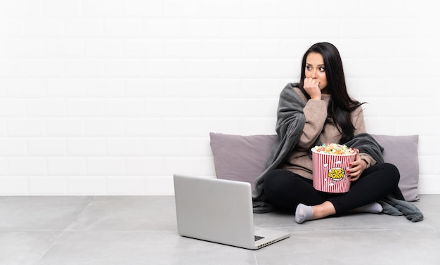 Young girl holding a bowl of popcorns and showing a film in a laptop nervous and scared putting hands to mouth