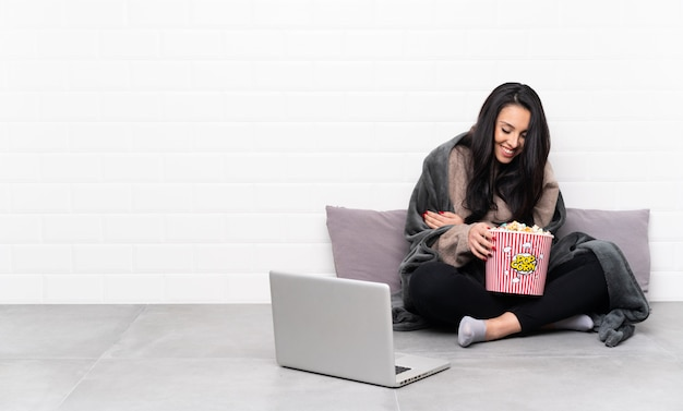 Young girl holding a bowl of popcorns and showing a film in a laptop smiling a lot