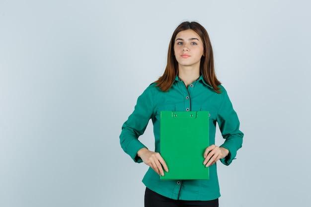緑のブラウス、黒のズボンで両手にクリップボードを保持し、真剣に見える少女。正面図。