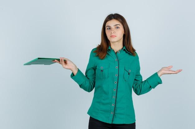 クリップボードを持って、緑のブラウス、黒のズボンで無力なジェスチャーを示し、困惑しているように見える少女、正面図。