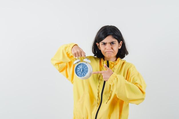 Молодая девушка держит часы и указывает на них указательным пальцем в желтой куртке-бомбардировщике и выглядит сердитой