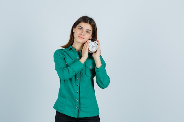 Young girl holding clock in both hands in green blouse, black pants and looking sanguine. front view.