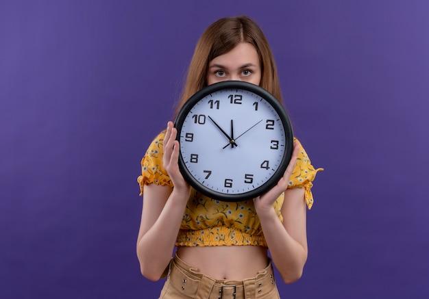 Ragazza che tiene l'orologio e nascondersi dietro di esso sulla parete viola isolata con lo spazio della copia