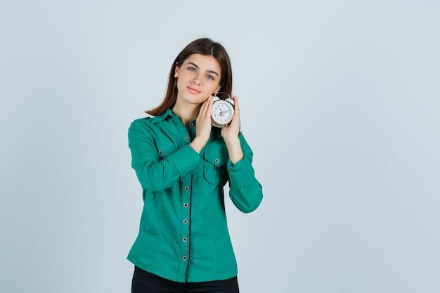 緑のブラウス、黒のズボンで両手に時計を持って、楽観的な若い女の子。正面図。