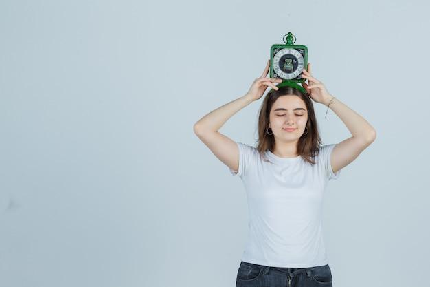 T- 셔츠, 청바지에 머리 위에 시계를 들고 재미 찾고 어린 소녀. 전면보기.