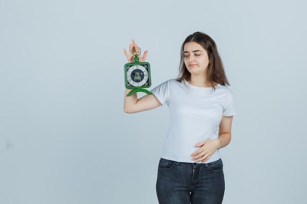 Tシャツ、ジーンズ、自信を持って、正面図でお腹に手を保ちながら時計を保持している若い女の子。