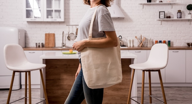 Young girl holding a cloth bag. at the kitchen. i am not plastic.