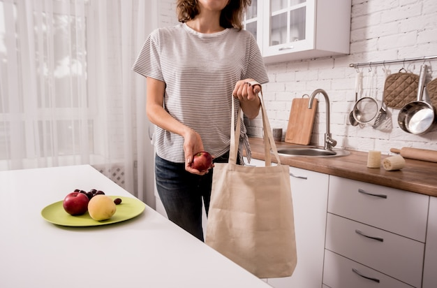 Young girl holding a cloth bag. at the kitchen.