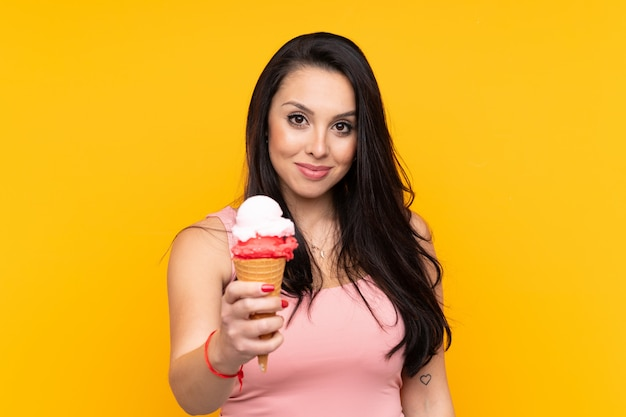 Young girl holding an cornet ice cream over yellow wall with happy expression