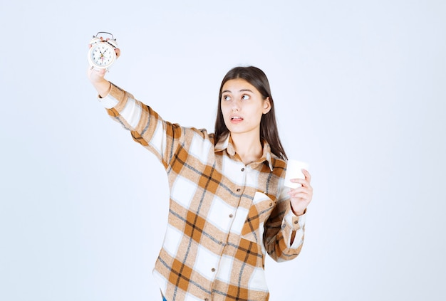Young girl holding cup of tea and looking at time on white wall.