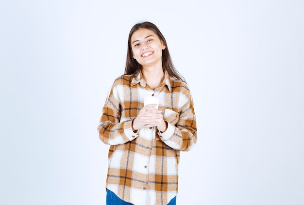 Young girl holding cup of tea on white wall.