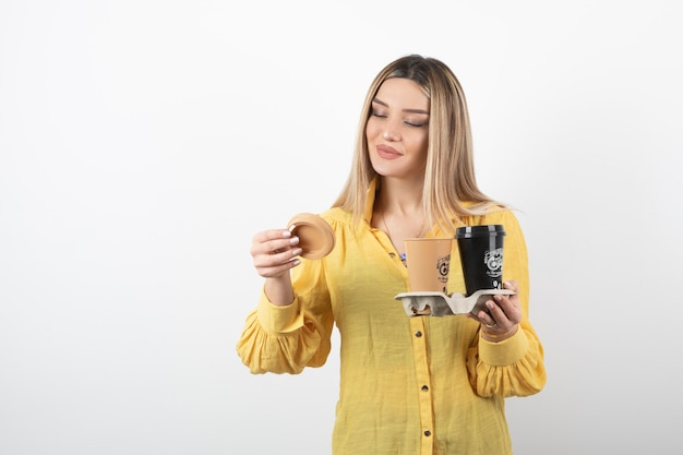 Giovane ragazza con tazze di caffè e guardando il coperchio.