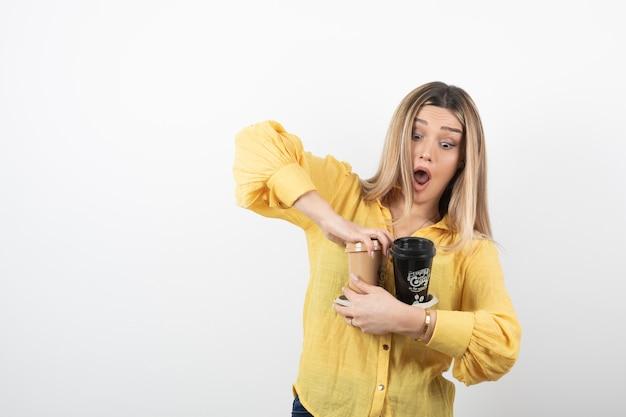 Giovane ragazza con tazze di caffè su bianco.