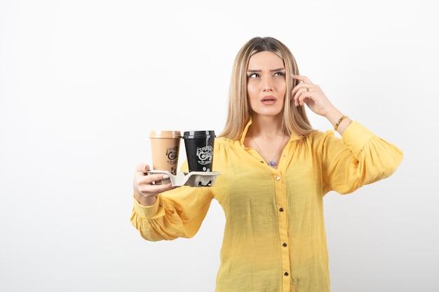 Молодая девушка держит чашки кофе и думает.